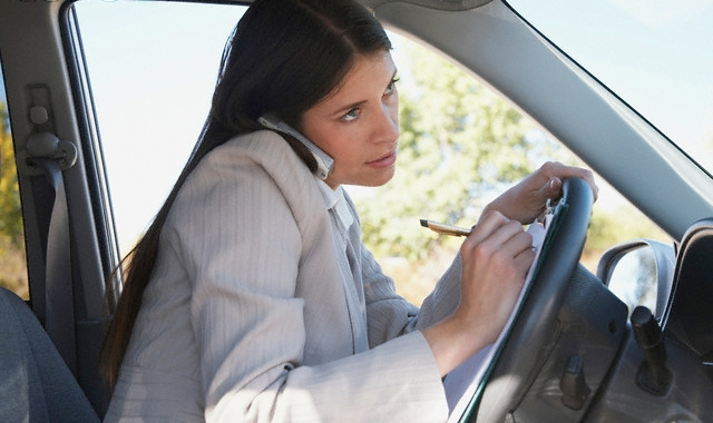 woman driving and using mobile