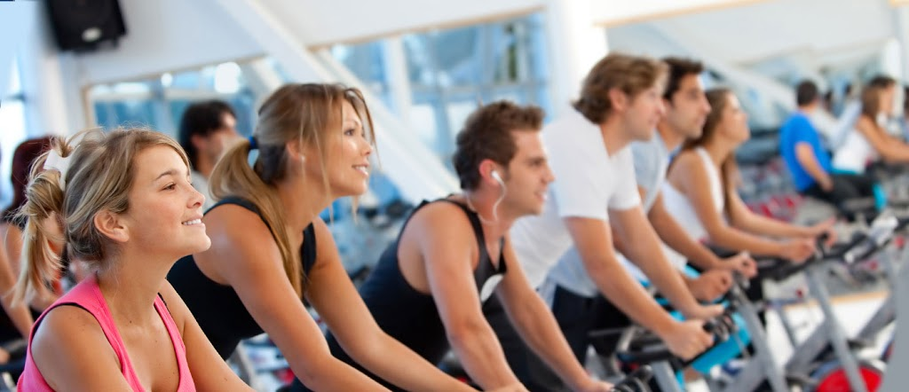 healthy and fit people on gym cycle